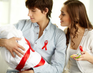 Young parents looking affectionately at their baby wrapped in blanket, with a red ribbon